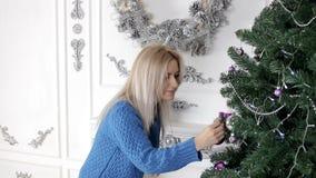Dame die de Kerstmisboom met speelgoed, gebieden verfraaien stock videobeelden