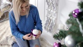 Dame die de Kerstmisboom met witte kaarsen verfraaien, het glimlachen stock video