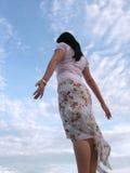 Dame, die dem Wind mit Himmel glaubt Lizenzfreie Stockfotografie