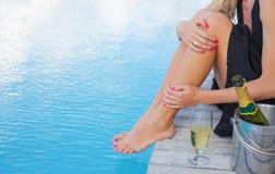 Dame, die durch das Pool, Fokus auf Champagnerglas sitzt Stockfotos