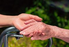 Dame die een bejaarde` s hand houden stock afbeelding