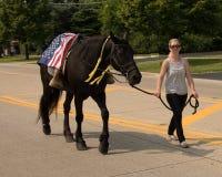 Dame die een riderless paard met laarzen achteruit in de stijgbeugels leiden royalty-vrije stock foto