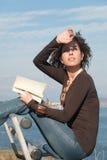 Dame, die ein Buch an der Küste liest Stockbild
