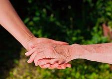 Dame, die eine ältere woman's Hand hält stockfotografie