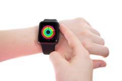 Dame, die eine Apple-Uhr mit Tätigkeits-flüchtigem Blick trägt Stockbild