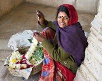 Dame, die eine Girlande außerhalb eines Tempels herstellt Stockfotos
