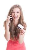 Dame, die eine Kreditkarte bei der Unterhaltung am Telefon zeigt Lizenzfreies Stockfoto