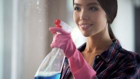 Dame die gemakkelijk vensters en spiegels van stof en vlekken met nieuw detergens schoonmaken royalty-vrije stock afbeeldingen