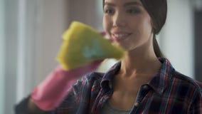 Dame die gemakkelijk vensters en spiegels van stof en vlekken met nieuw detergens schoonmaken stock video