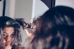 Dame, die ihr Haar mit Haarbürste am Spiegel kämmt lizenzfreie stockbilder