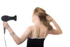 Dame, die ihr Haar mit hairdryer trocknet Stockbild