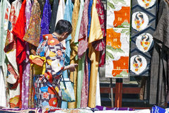 Dame die Kimono van kleurrijke inzameling in een winkel van de Kimonohuur op Matsubara-straat in Kyoto, Japan selecteren stock foto's
