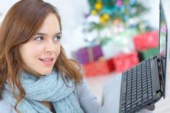 Dame die laptop met behulp van bij Kerstmis stock foto