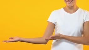 Dame die lege die plaats voor reclame of tekst tonen op oranje achtergrond wordt geïsoleerd stock footage