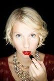 Dame die lippenstift zetten (als voor een spiegel) Royalty-vrije Stock Foto