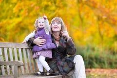 Dame, die mit kleinem Kleinkindmädchen im Herbstpark spielt Lizenzfreies Stockfoto