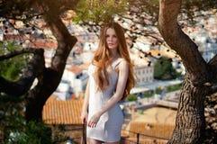 Dame, die nahe Kiefer, Europa-Stadt auf dem Hintergrund aufwirft stockbilder