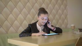 Dame die op de telefoon spreken en een tablet in koffie gebruiken 4K stock video