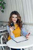 Dame die telefoon in een koffie met behulp van Stock Foto