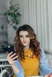 Dame die telefoon in een koffie met behulp van Royalty-vrije Stock Fotografie