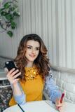 Dame die telefoon in een koffie met behulp van Stock Fotografie