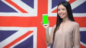 Dame die telefoon met het groene scherm tonen tegen Britse vlag op achtergrond, app stock videobeelden