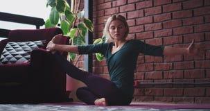 Dame die thuis yoga in haar ruimte ontspannen uitoefenen zij het uitrekken zich benen en lichaam om meer energie voor te worden d stock videobeelden