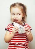 Dame die van die jonge leeftijd chocolade eten in aluminiumfolie wordt verpakt royalty-vrije stock afbeeldingen