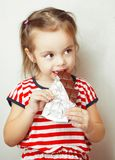 Dame die van die jonge leeftijd chocolade eten in aluminiumfolie wordt verpakt royalty-vrije stock foto's