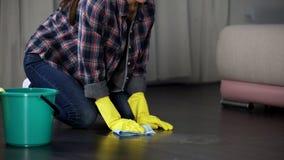 Dame die vlekken op vloer met speciaal vlekkenmiddel, oppoetsende vloeistof proberen van de hand te doen royalty-vrije stock afbeeldingen