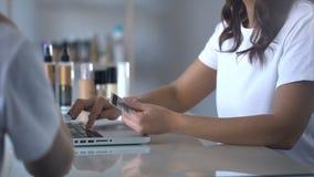 Dame die voor de dienst van schoonheidssalon door kaart betalen, vrouwelijkheid, comfortabel bankwezen stock footage