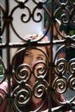 Dame durch aufwändige Fensterstangen stockfoto
