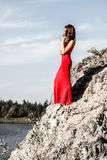 Dame in een rode kleding op de rivierrand stock foto's