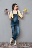 Dame enceinte choisissant entre le gâteau et la pomme doux Images stock