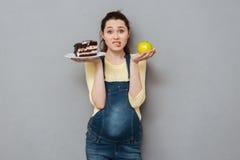 Dame enceinte choisissant entre le gâteau et la pomme doux Photographie stock libre de droits