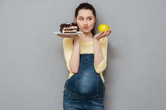 Dame enceinte choisissant entre le gâteau et la pomme doux Photo stock