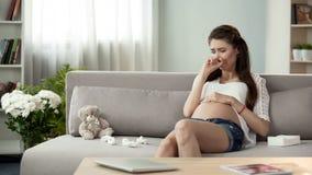 Dame enceinte contrariée pleurant sur le sofa, problèmes émotifs de désordre hormonal image stock