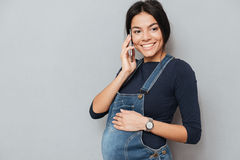Dame enceinte de sourire parlant par le téléphone Photos libres de droits