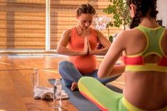 Dame enceinte intéressée au yoga Images libres de droits