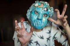 Dame fantasmagorique avec le masque faisant la magie avec ses doigts photographie stock libre de droits