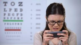 Dame gamer in oogglazen die op smartphone, risico spelen om gezicht, verslaving te verliezen stock footage