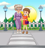 Dame âgée de aide de fille traversant la route Image stock