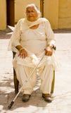 Dame âgée s'asseyant avec un bâton de marche Photos libres de droits