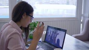 Dame in glazen de belast met zelfontplooiing gebruikt laptop computer voor afstandsonderwijs en maakt nota's in notitieboekje stock video