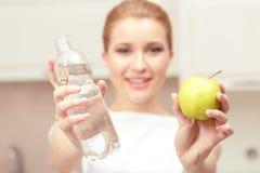 Dame hält Flasche des Wassers und des Apfels Stockbild