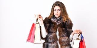 Dame halten Einkaufstaschen Rabatt und Verkauf Fashionistakaufkleidung an schwarzem Freitag Mädchenmake-uppelzmanteleinkaufen stockfoto