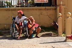Dame handicapée sur le fauteuil roulant avec d'autres mendiants masculins à la cour d'église priant pour l'aumône image libre de droits