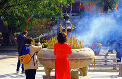 Dame in het rode bidden met wierookstokken stock afbeeldingen