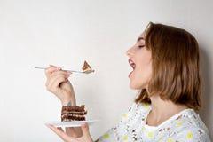 Dame heureuse de brune avec le maquillage naturel mangeant le gâteau de chocolat sucré L'espace pour le texte photographie stock
