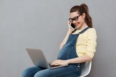 Dame heureuse enceinte à l'aide de l'ordinateur portable et parlant par le téléphone Photo stock